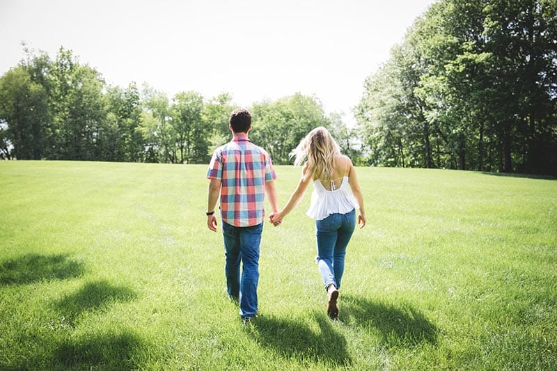 Couple holding hands while walking on grass