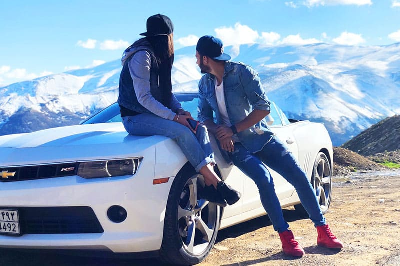 Couple leaning on white chevrolet coupe staring at mountains