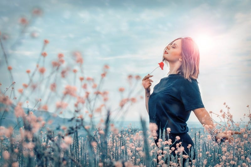 woman standing and holding red flower in field