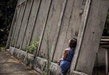 girl sitting alone beside concrete wall