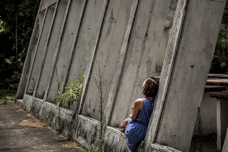 girl sitting alone beside concrete wall