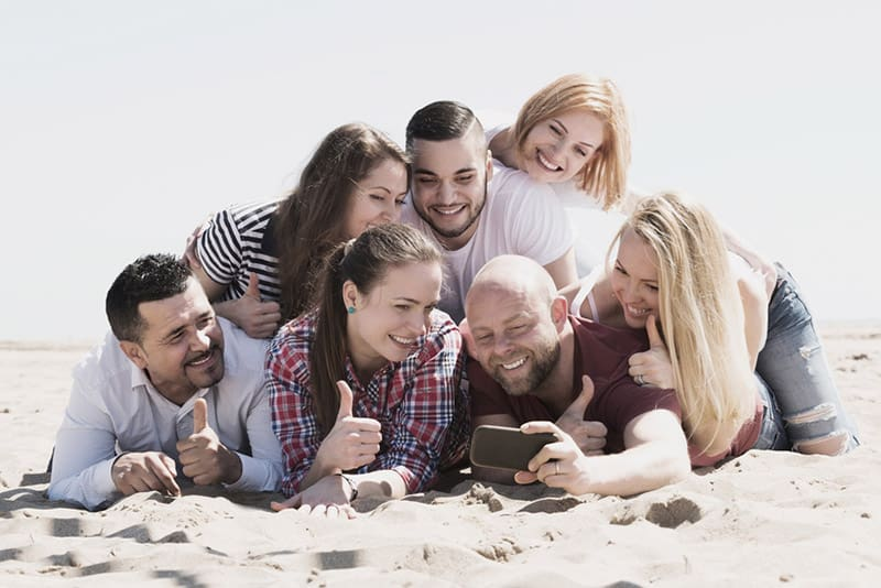 Group picture of friends posing on the beach floor