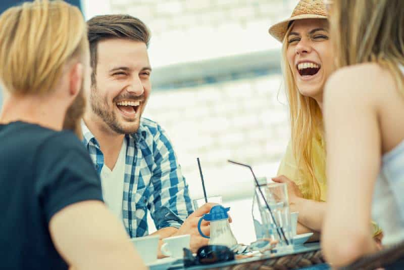 Friends smile and sit in a cafe, drink coffee and enjoy together