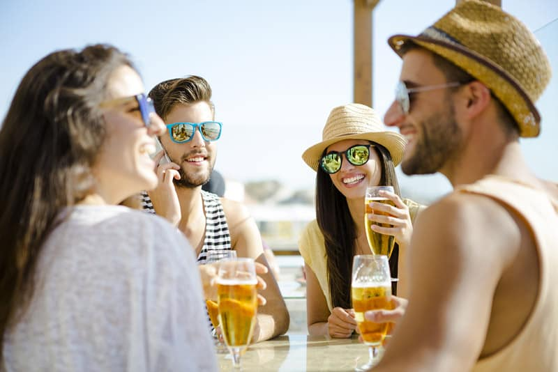 friends talking and drinking with sunglasses on by the beach