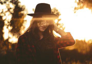 cute woman wearing hat on sunset