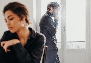 man smoking near the window far behind a woman sitting