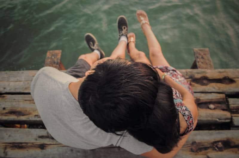 Man and woman hug on brown wooden dock