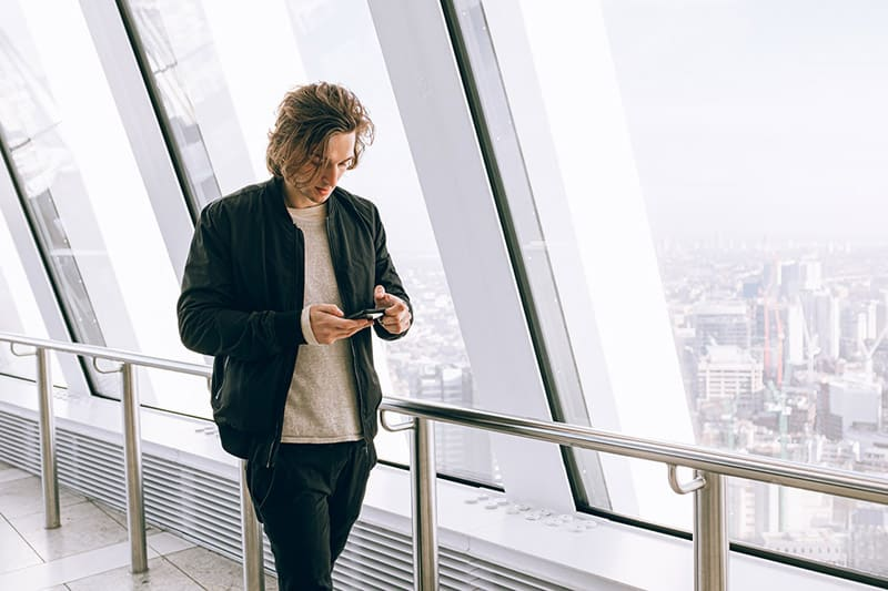 Man texting on phone wearing black jacket beside large window
