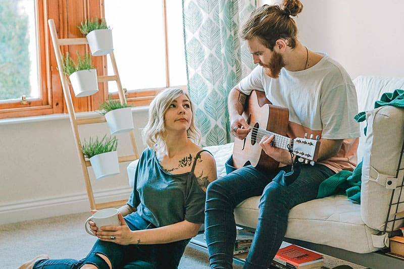 Man plays guitar while woman watches and holds a coffee mug