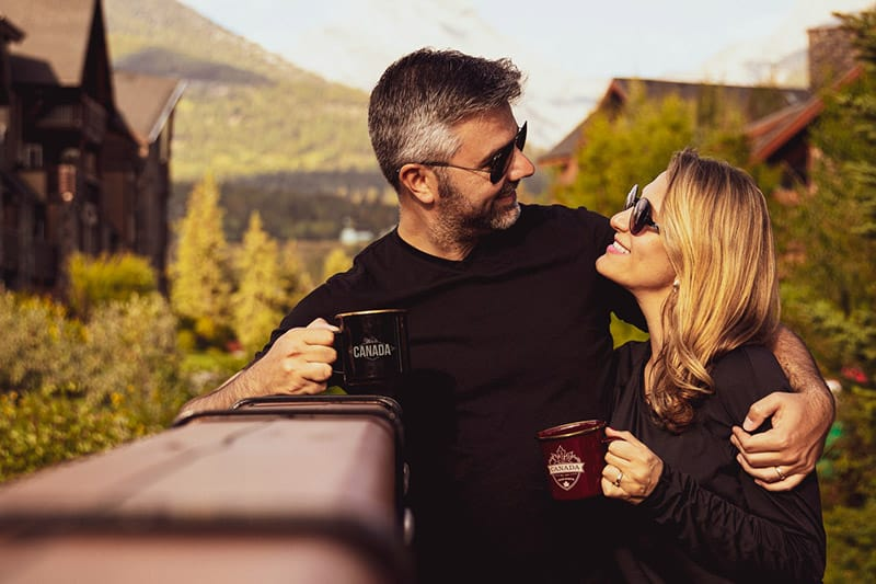 Couple having coffee with man hugging woman