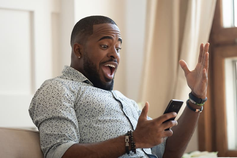 Man in shock while looking at phone