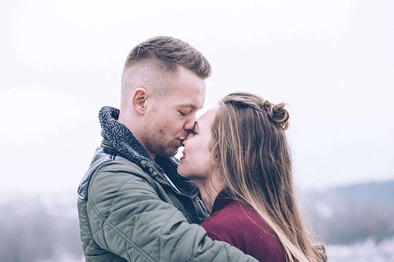 Couple hugging with man kissing woman's nose