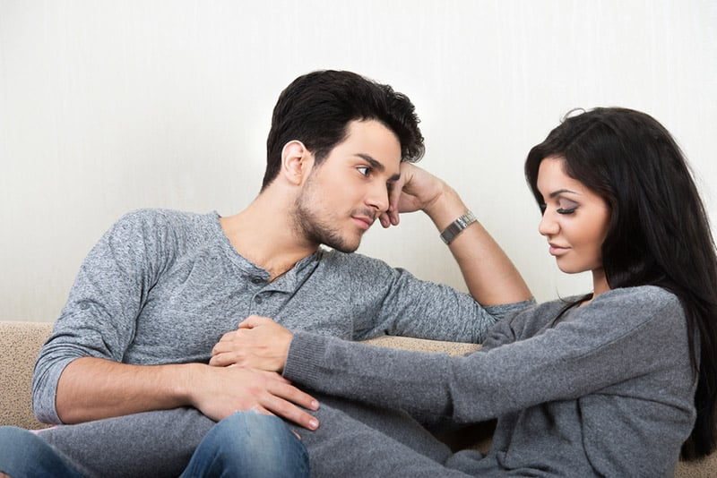 Man propped on his elbow staring at woman while she looks down