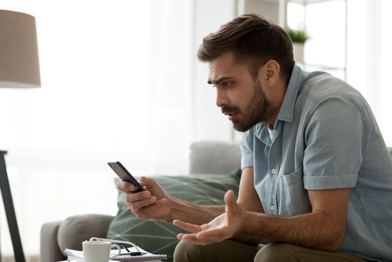 Man on living room sofa looking frustrated while using phone