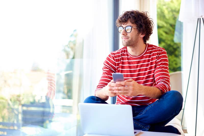 Man wearing red and white striped shirt using phone while looking out in the distance