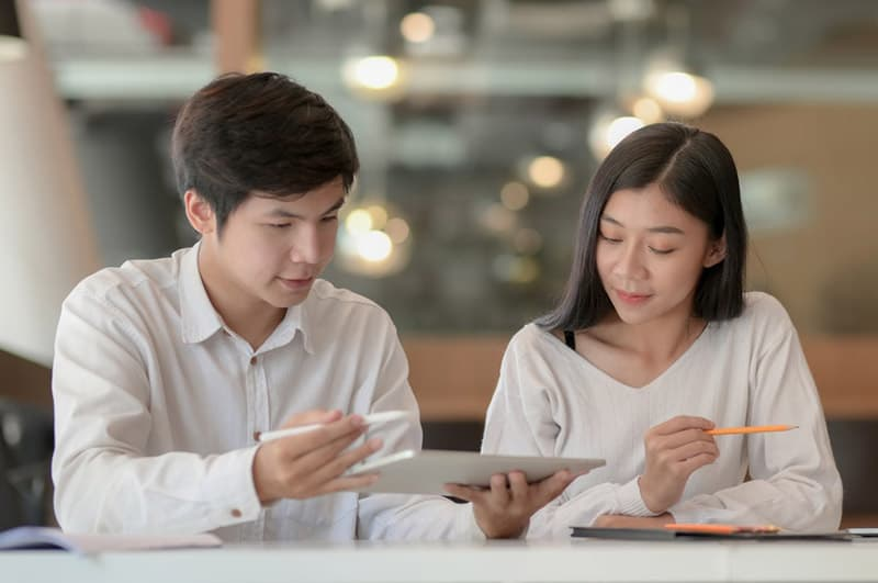 Man discusses plan with woman using a tablet