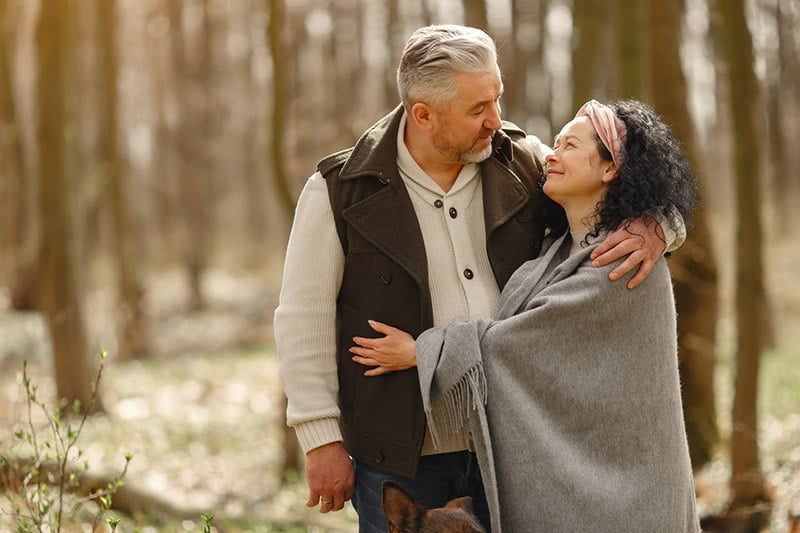Older couple hugging outdoors and staring at each other