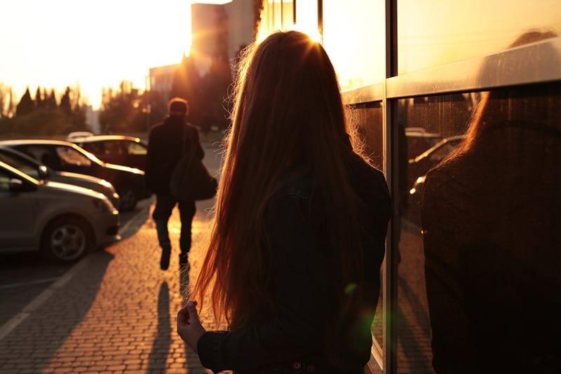 Quarrel man walks away while woman leans on bus