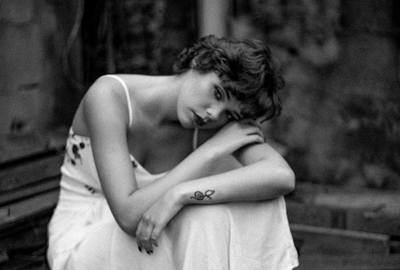 sad woman in white dress leaning her head to her arms