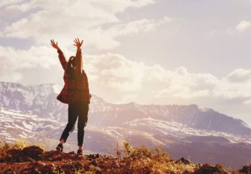 happy woman raising hands up on mountain