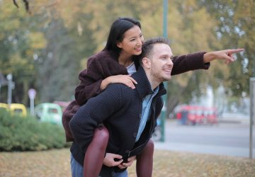 man giving a piggyback to a woman pointing her hand