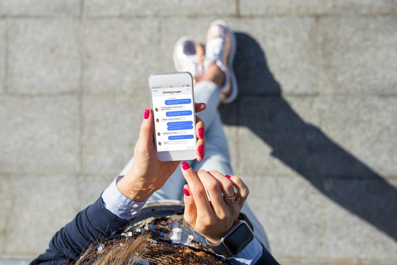 Top view of phone messages while person is walking