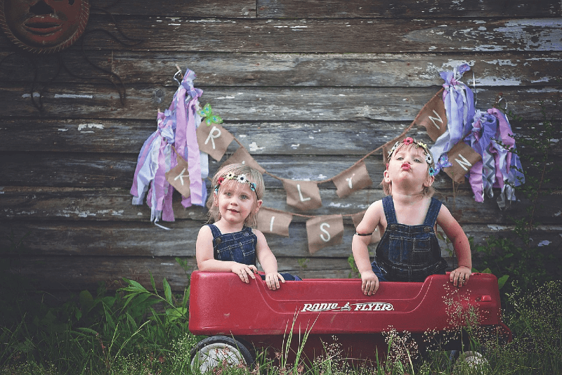 female twins standing in wagon outdoor