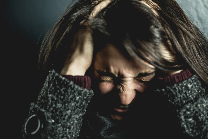 woman holding head like it was painful