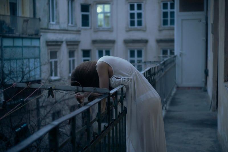 woman leans on railing wearing lingerie