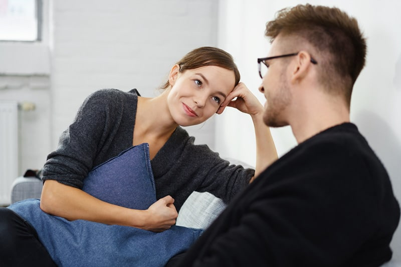 Woman gazes at man while they're talking on the sofa