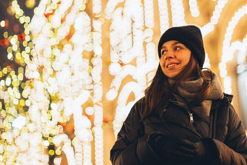 Woman wearing black bubble jacket and beanie in front of lights