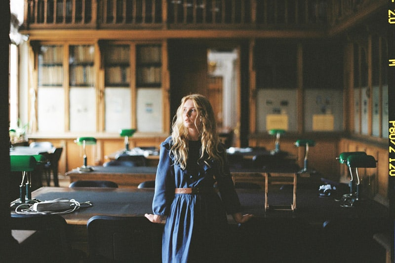 Woman wearing a blue dress inside a library