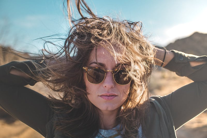 Woman holding on to curly hair in windy outdoor