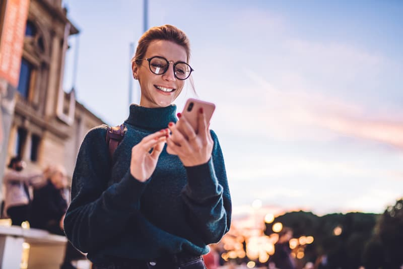 Woman in turtleneck and wearing glasses smiling at her phone