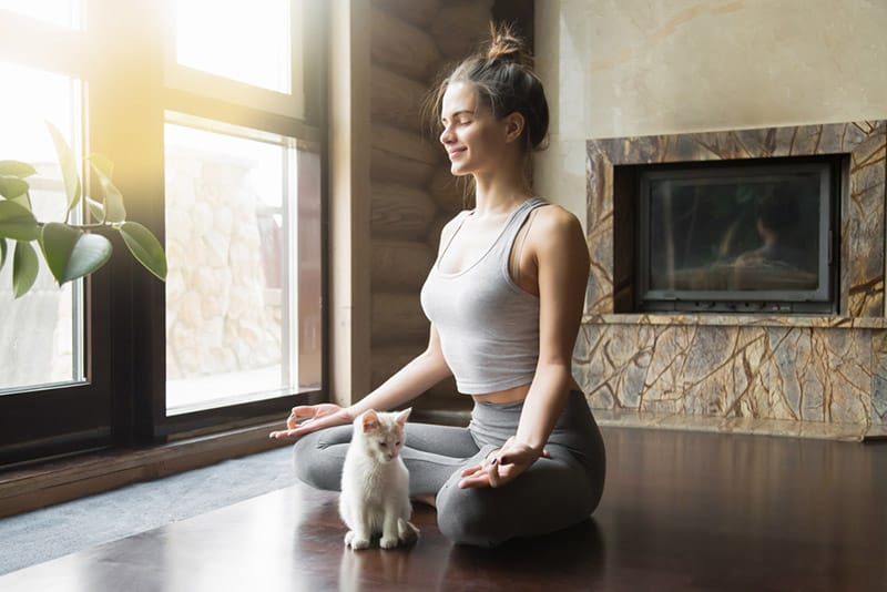 Woman with hair up on a bun sitted on the floor practicing yoga