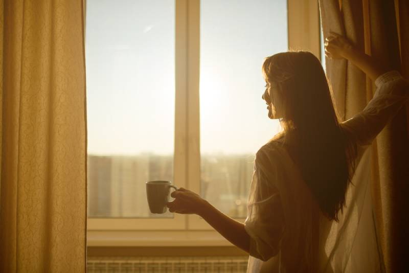 Woman holds a cup of hot tea and looks at the sunrise