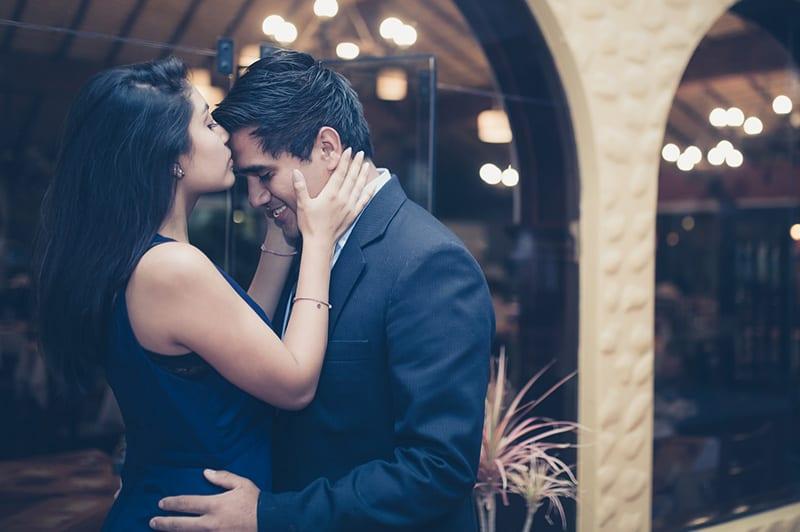 Woman on tiptoe kisses man's forehead