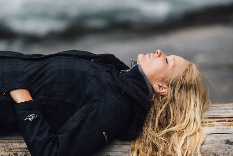 Woman wearing black jacket lies down on a large log by the beach