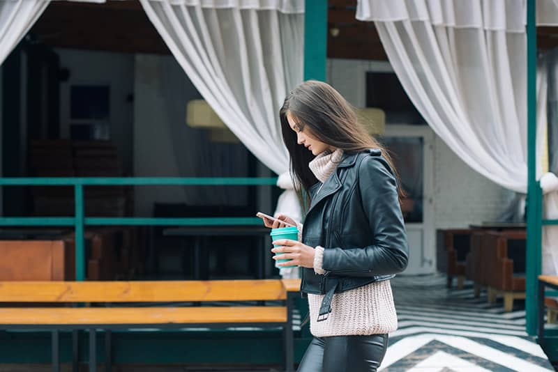 Woman in leather jacket texting while walking