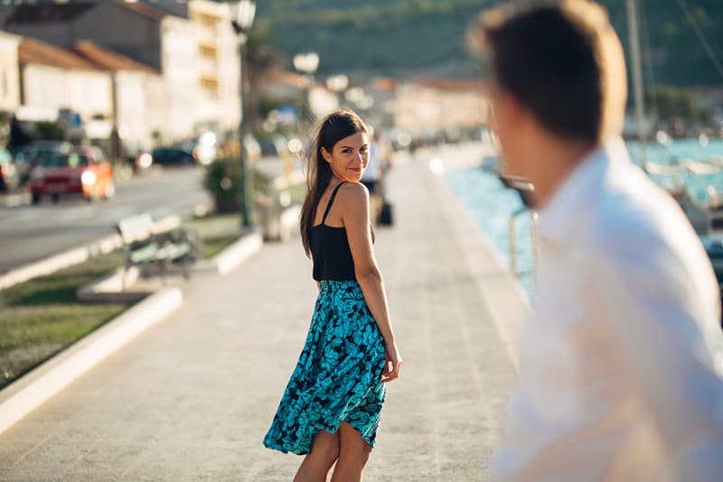 woman in blue dress looks back at man