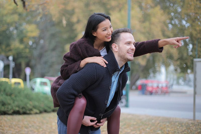 Woman piggyback on man at the park