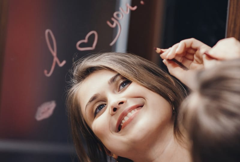 Woman smiling with I Love You written above reflection in mirror