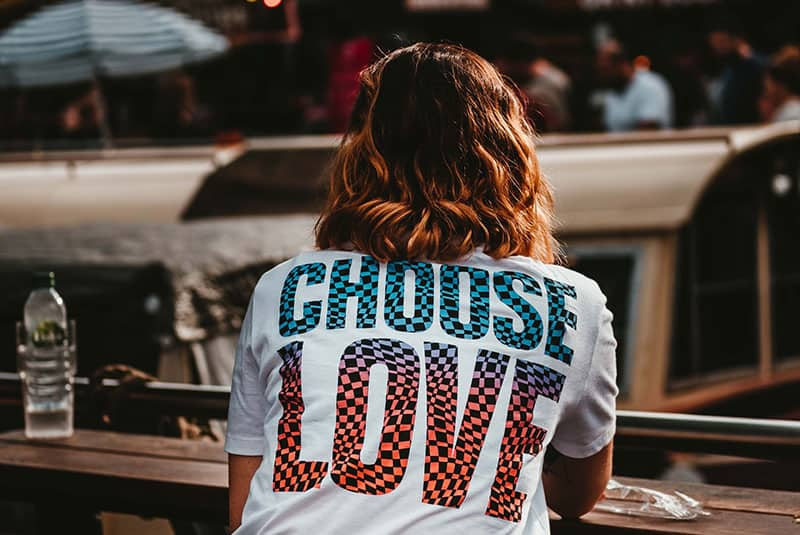 Woman wearing white shirt with words Choose Love