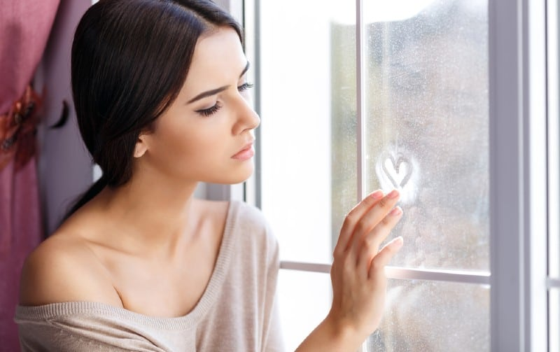 Beautiful girl sitting at the window and painting with her finger a heart on the glass