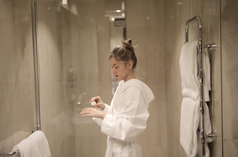 Woman inside bathroom wearing bathrobe and putting on Lotion on hands