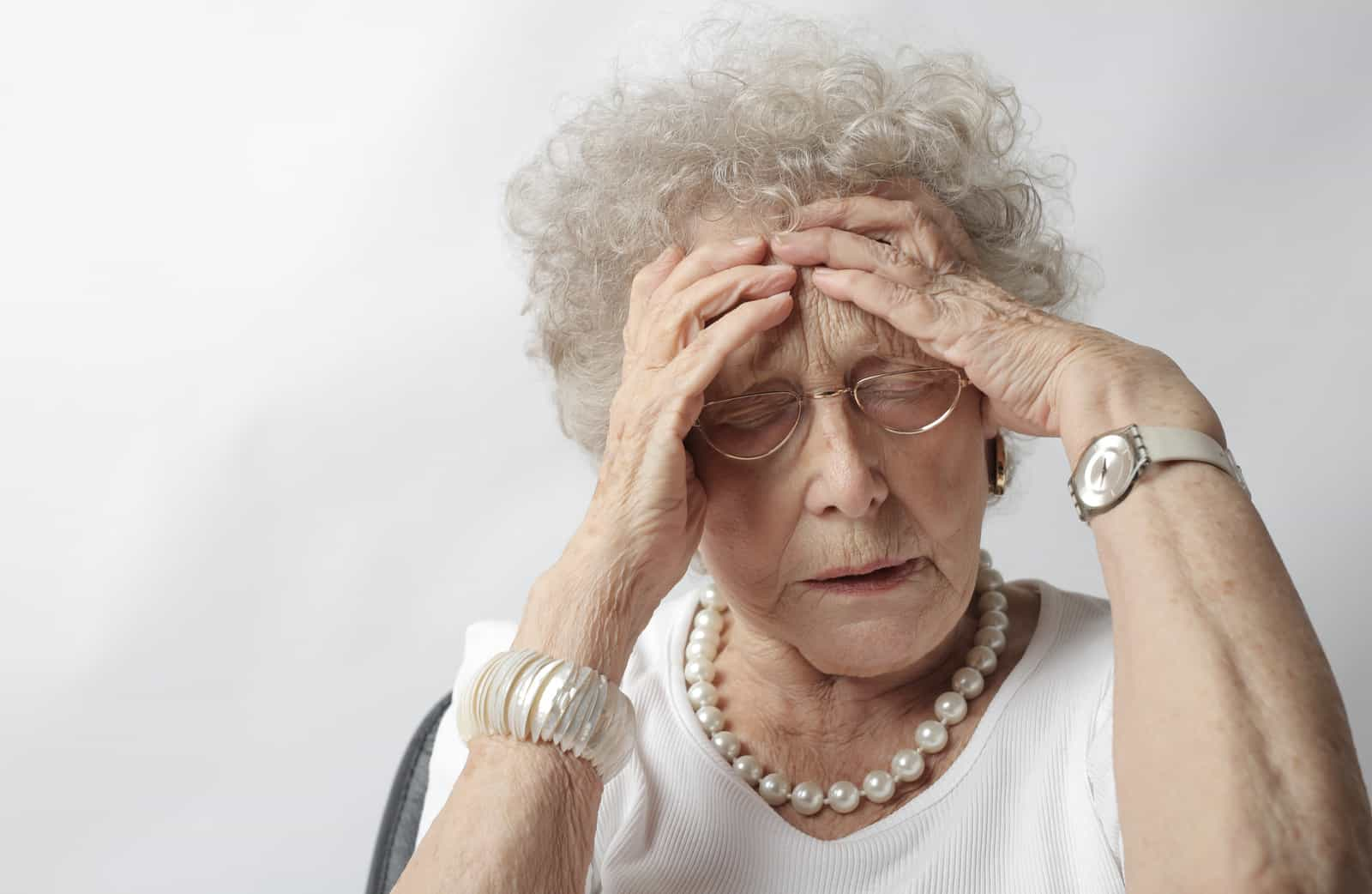 woman with headache holding her head wearing white top