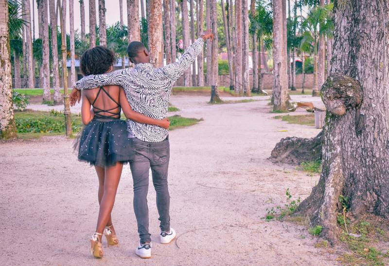 Young couple walking in the park with guy pointing