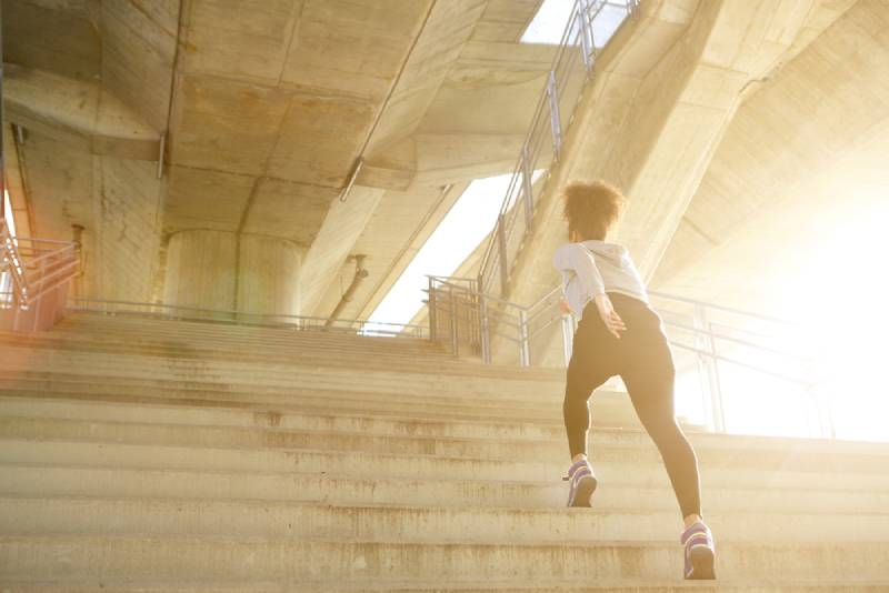 Young exercises woman running alone upstairs