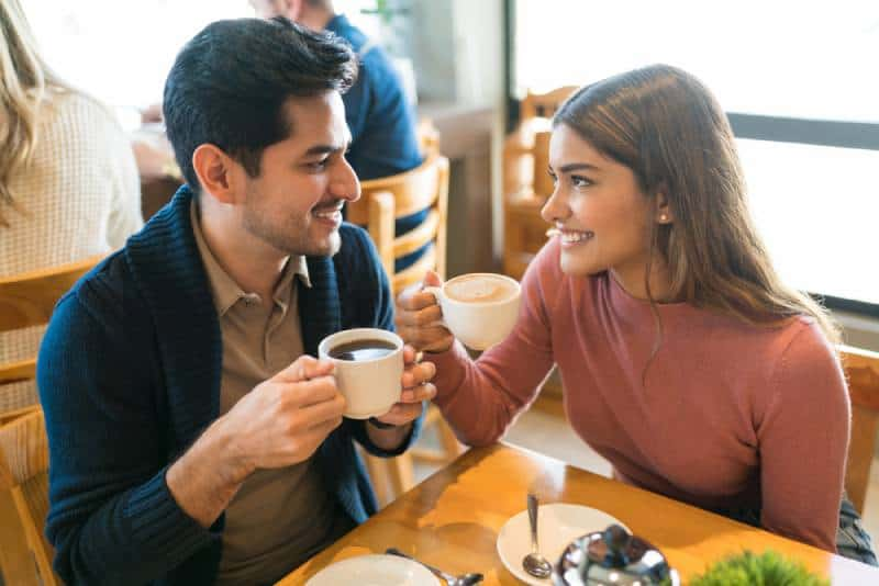 Young lovers enjoy coffee while looking at each other in a cafe