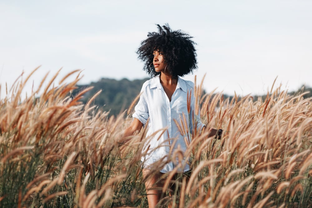 a black woman in a white shirt walks through a field of wheat